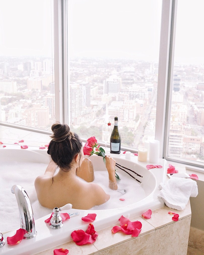 Enjoying champagne in jacuzzi tub with roses surrounding it
