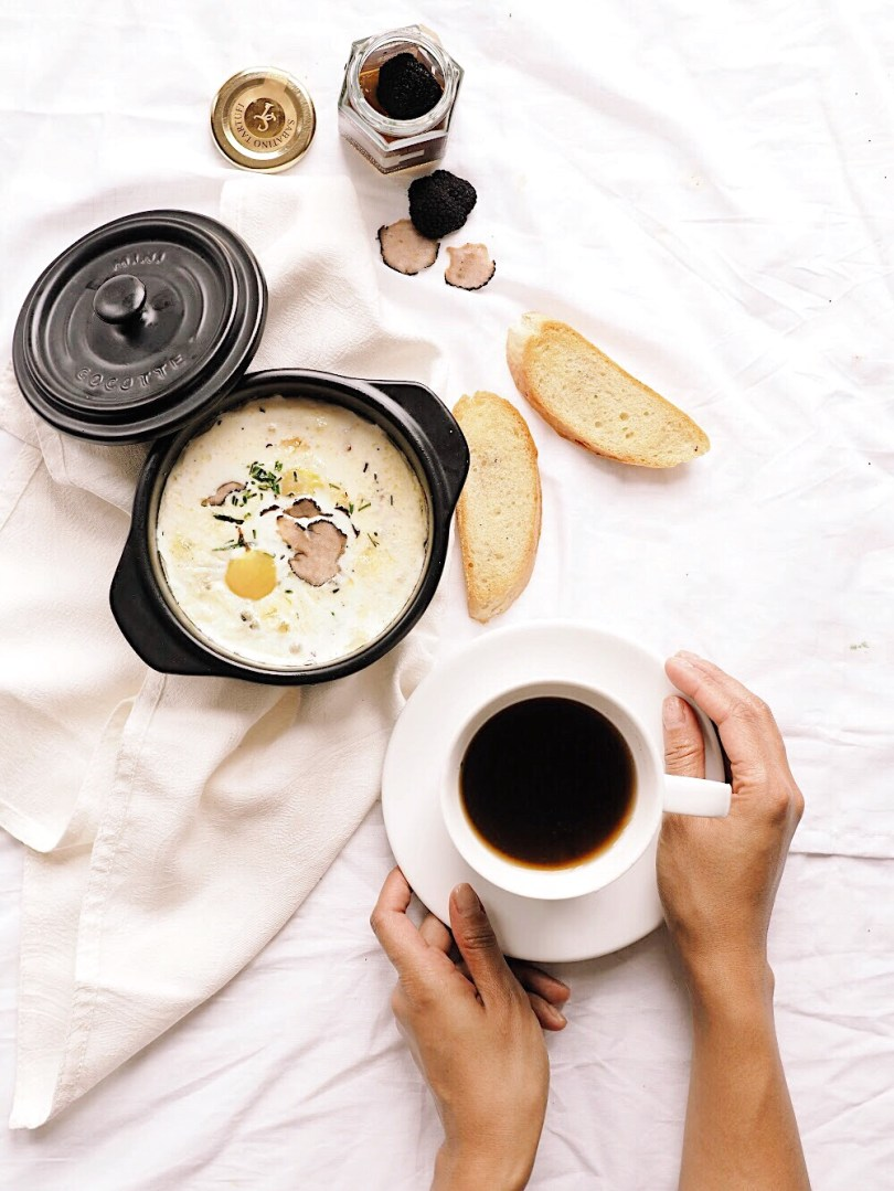 Eggs en Cocotte with hands on coffee