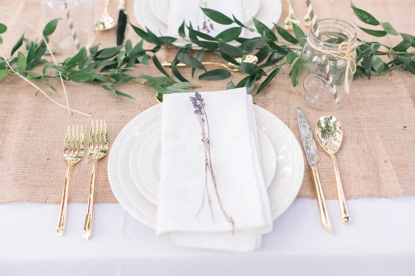 White dinner plates with gold cutlery, white linen napkins, lavender
