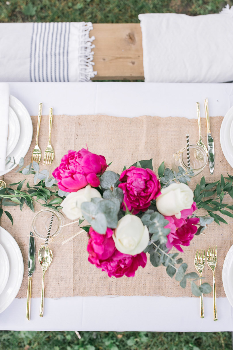 Picnic table with white tablecloth, burlap runner, Italian Ruskus and centerpiece