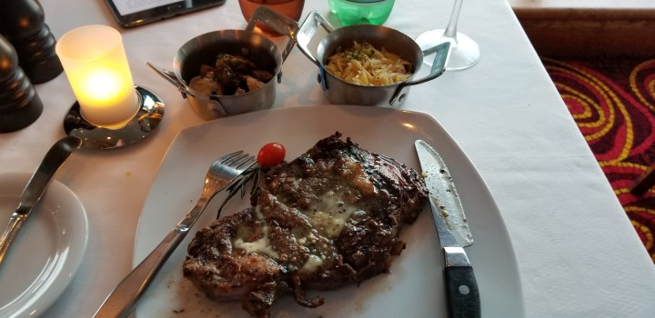 Ribeye with garlic butter at Cagney's Steakhouse on the Norwegian Sky. Also pictured are the roasted mushrooms and orzo pilaf I requested as sides.