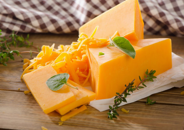 Cheddar Cheese on  a rustic wooden background. Selective focus