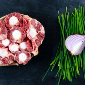Fresh Raw Beef Oxtail Meat cut, ready to cook. with vegetable. on Blue stone  Background