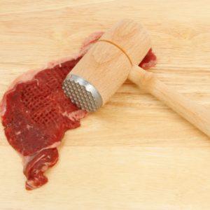 Piece of sirloin steak with a tenderiser on a wooden board
