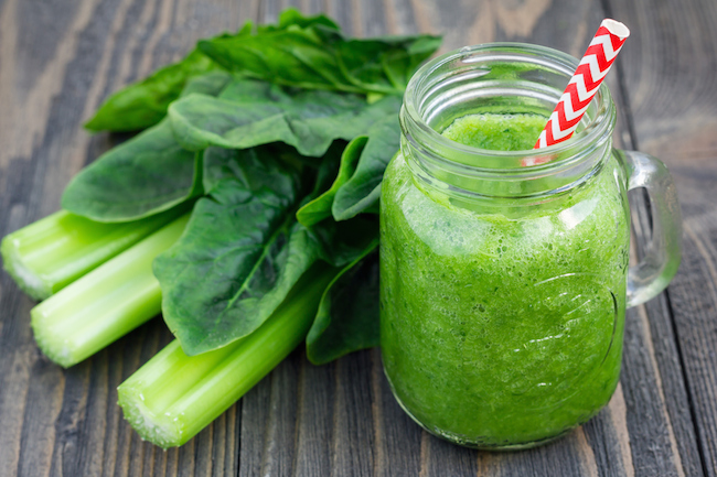 Green smoothie with celery, cucumber, spinach, apple, lemon in glass