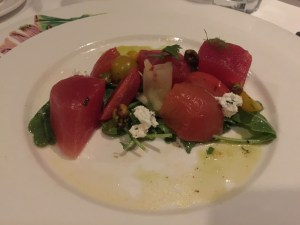 Caribbean watermelon salad: Caribbean rum and lime compressed watermelon with chili and basil soaked yellow tomotoes, goat cheese, cayenne pistachios and basil-watermelon vinaigrette