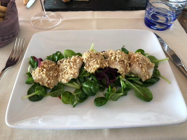 Baked monkfish with crust of mix nuts on raw spinach, sundried tomatoes and red onion