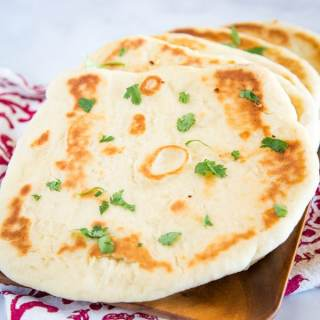 Naan Bread - This homemade naan bread is a soft and chewy Indian style flatbread.  A simple and easy dough that makes for the most delicious bread!  It is great to brush with butter and garlic for an easy garlic naan recipe.