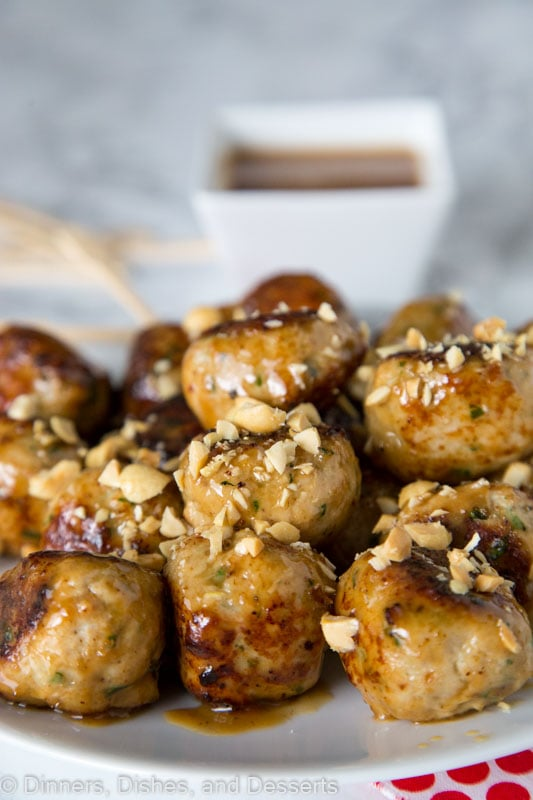 a plate of chicken meatballs with chopped peanuts