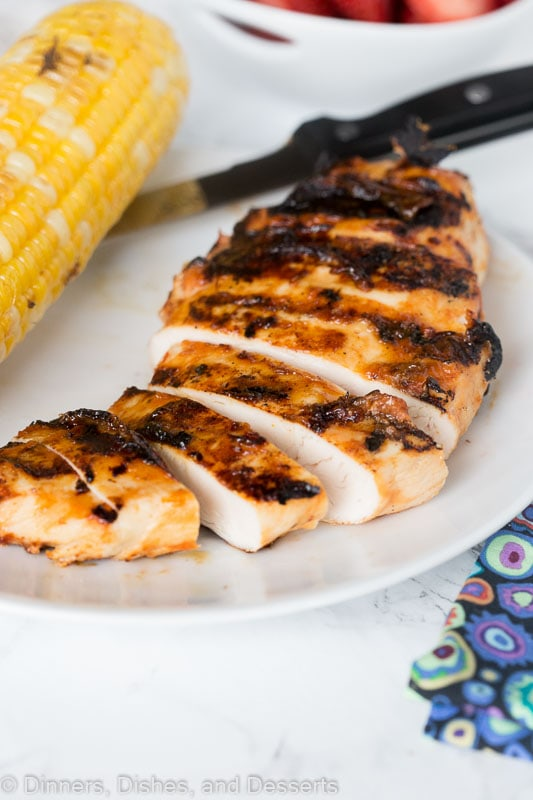 sliced barbecue chicken on a plate next to corn on the cob