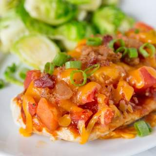 A close up of a plate of food with chicken topped with tomatoes, bacon and melted cheese