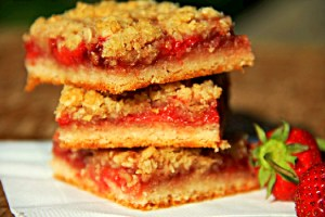 Strawberry Crumb Bars stacked on white napkin