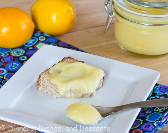 lemon curd on bread on white plate with lemons on background