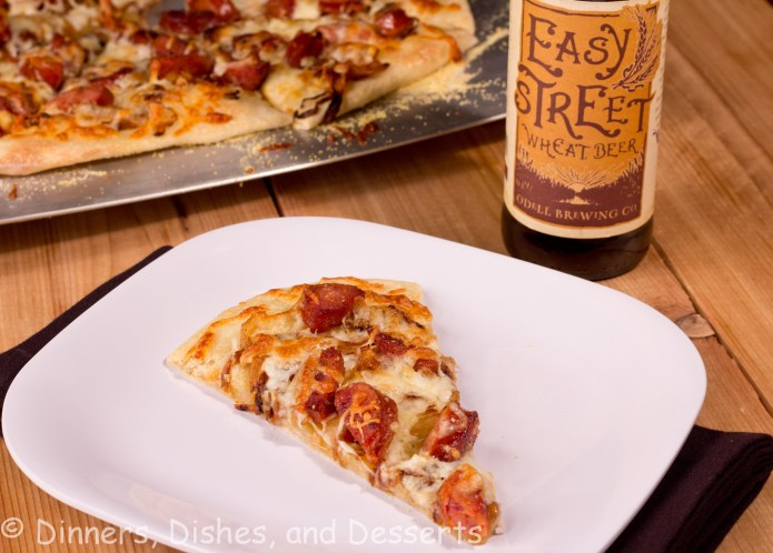 Caramleized Onion and Andouille Pizza on white plate with bottle of beer in background