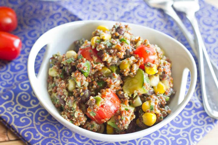 Quinoa Salad with corn, black beans, grape tomatoes, and zucchini, then topped with a creamy avocado dressing. Great warm or cold, so it is perfect for a picnic or barbeque