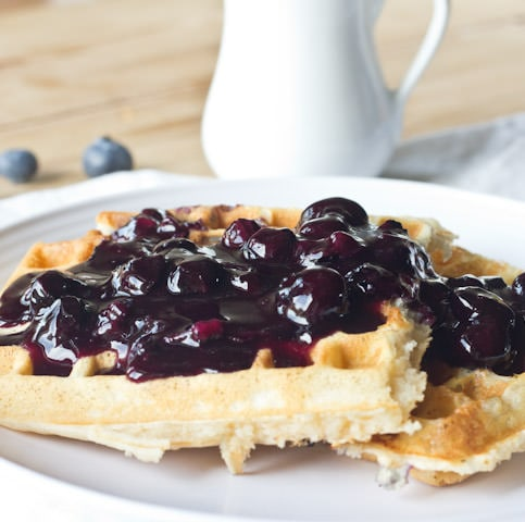 waffles on a plate with blueberry sauce