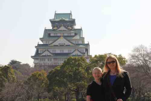 A person standing in front of Osaka Castle