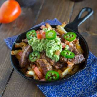 Carne Asada Fries - french fries topped with Carne Asada, melted cheese, and guacamole!