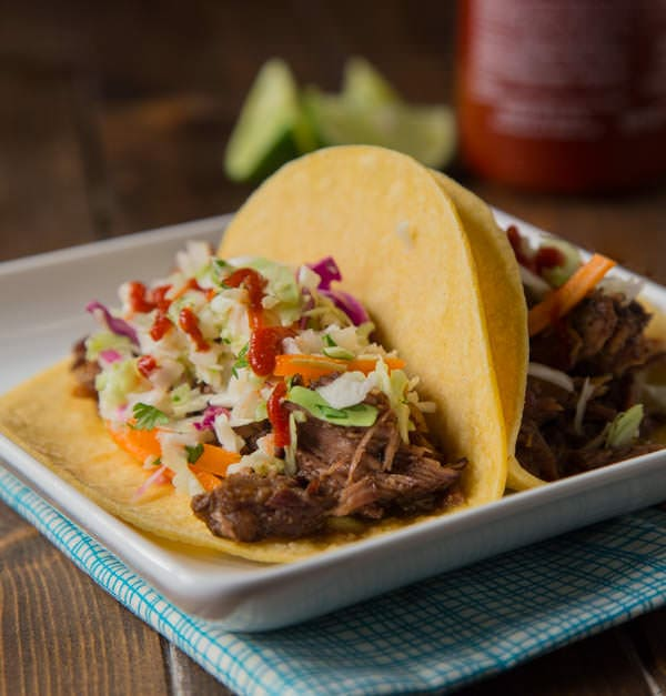Slow Cooker Korean Beef Tacos - Let your crock pot do the work and get perfectly tender, sweet and spicy beef that is perfect piled on a tortilla topped with a little Korean coleslaw.