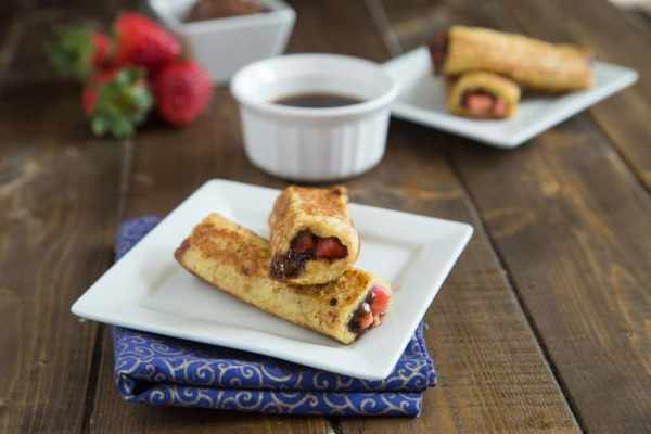 French toast rolls ups are a fun new twist on a classic.  Filled with chocolate hazelnut spread and strawberries these are sure to please!