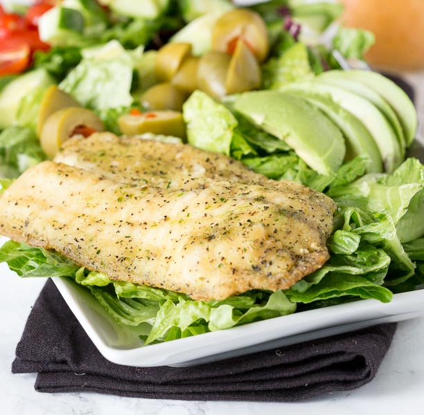 Garlic & Herb Mediterranean Salad - A crisp salad with fresh salad with garlic & herb tilapia and topped with a lemon garlic vinaigrette.