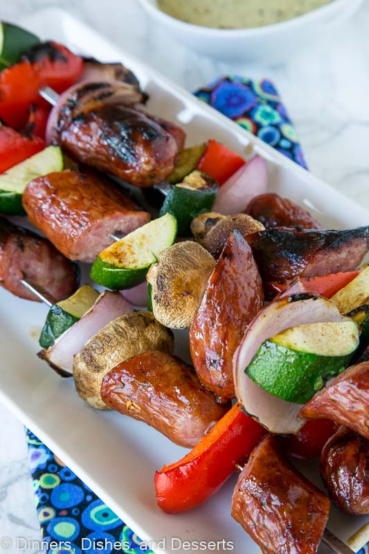 grilled sausage and veggie kebabs on a plate
