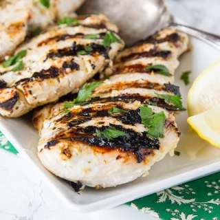 grilled chicken on a plate with lemon slices