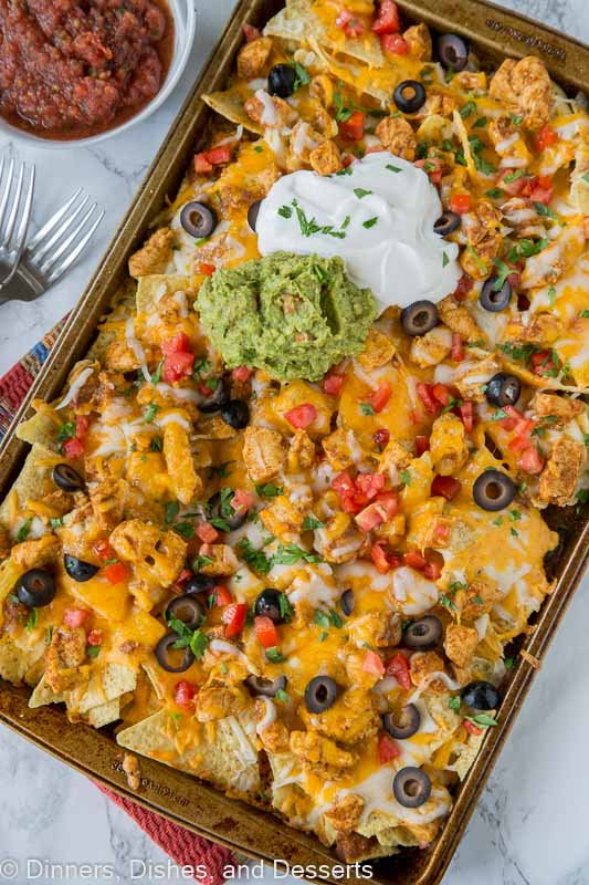 chicken nachos on a tray with guacamole and sour cream