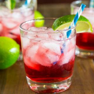 A glass of cranberry vodka on the table with limes