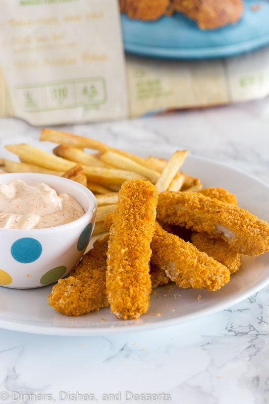 fish sticks on a plate with dipping sauce