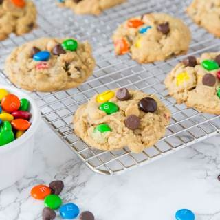 Soft Monster Cookies - a soft and chewy cookie that is a cross between a peanut butter cookie, an oatmeal cookie, and a chocolate chip cookie!  Full of lots of goodies everyone loves them!