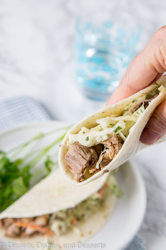 Instant Pot Pork Tacos - these pulled pork tacos are super tender and so delicious. Topped with a creamy Mexican slaw and avocado sauce!