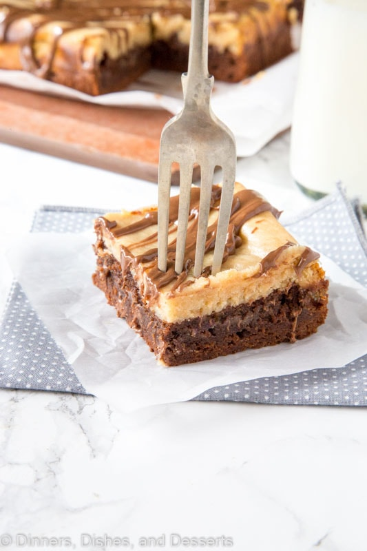 Peanut butter cheesecake brownie on a plate with a fork
