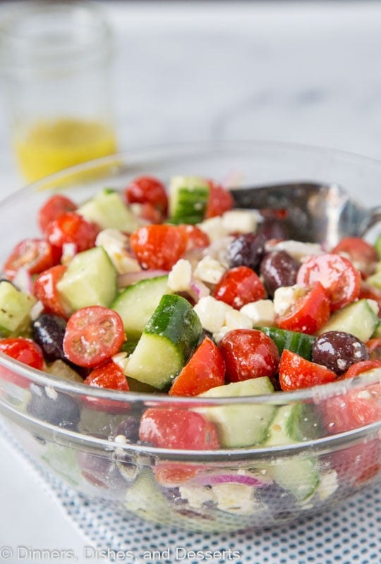 Easy summer salad with cucumbers, tomatoes, onions, olives and feta cheese topped with a lemony Greek dressing