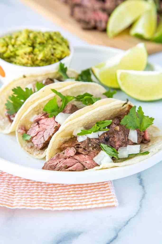 Flank Steak Tacos topped with onions and fresh cilantro