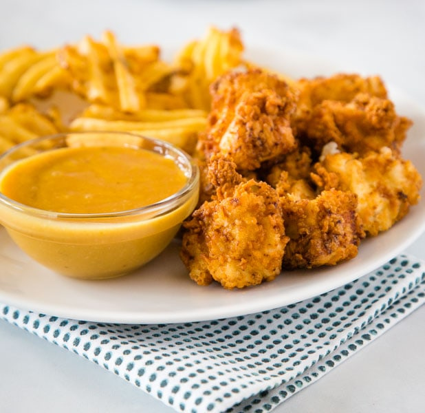 chick fil a chicken nuggets on a plate with fries and dipping sauce