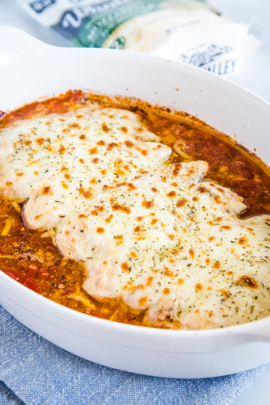 Easy Baked Chicken with garlic butter, diced tomatoes and lots of cheese