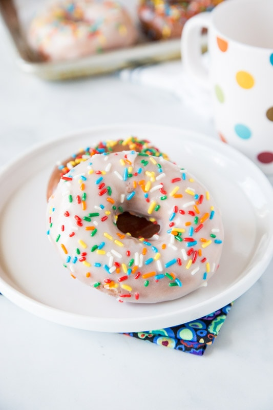 Raised donuts with white icing and sprinkles