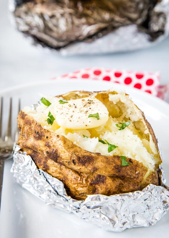 grilled baked potato on white plate with butter and chives