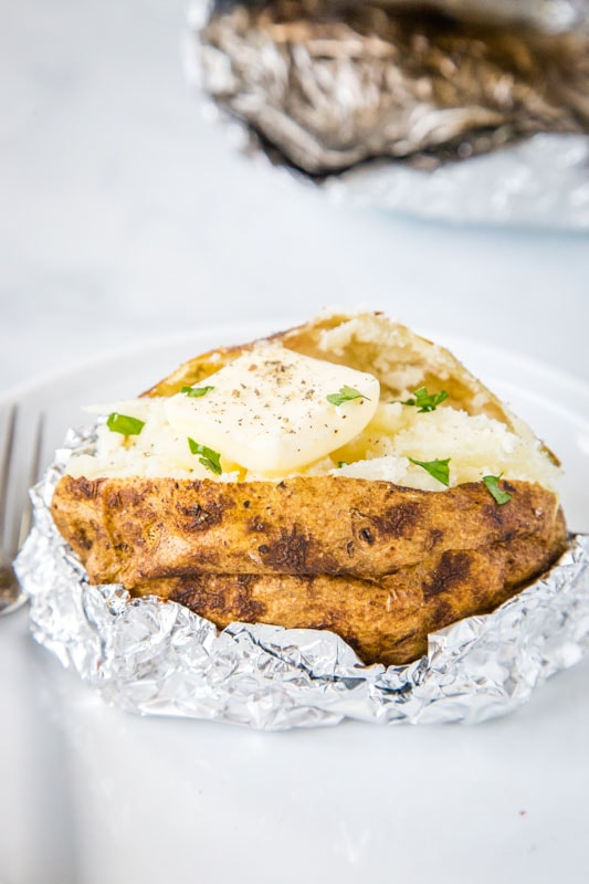 baked potatoes on the grill with butter and chives