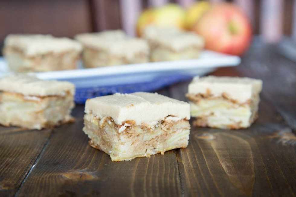apple brownie with cinnamon frosting on a wood table