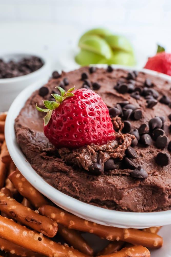 chocolate hummus in white bowl with strawberries