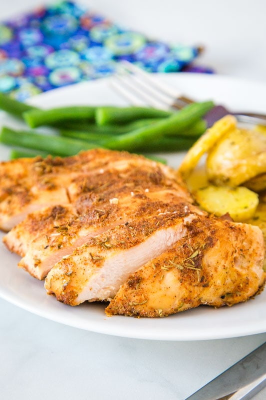 Cut up chicken breast on plate with green beans and potatoes