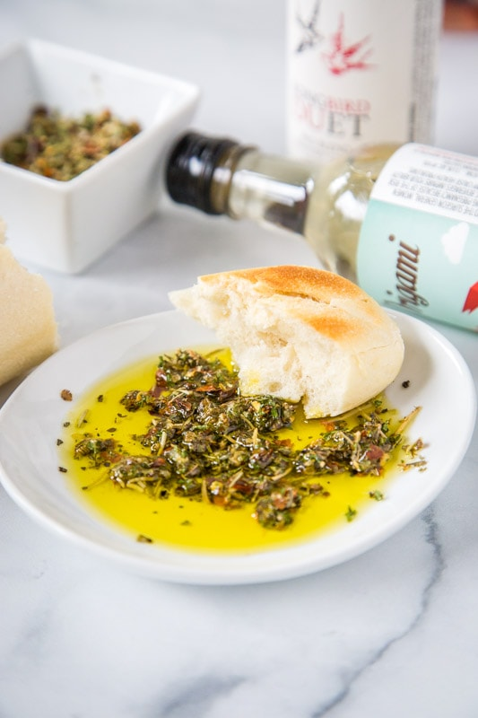 olive oil bread dip with bottle of wine