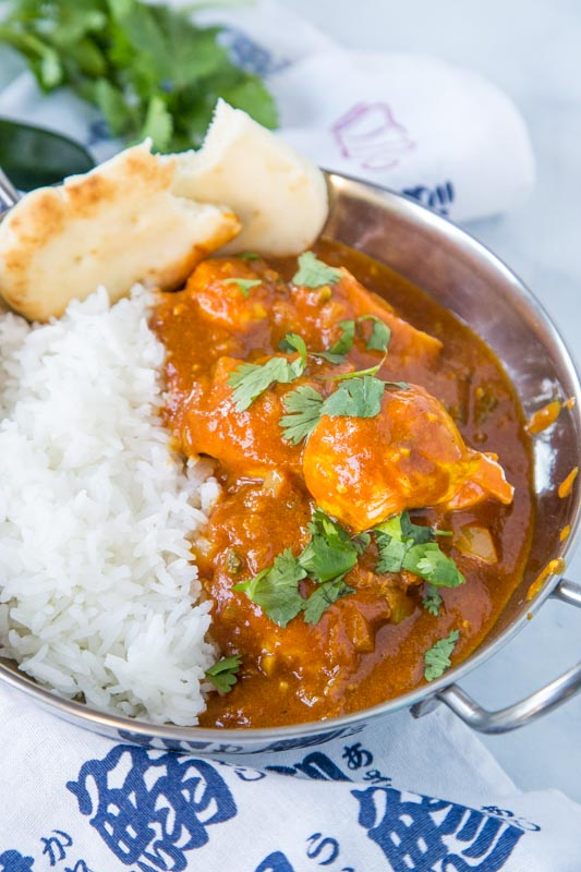 vindaloo curry in bowl with rice and naan