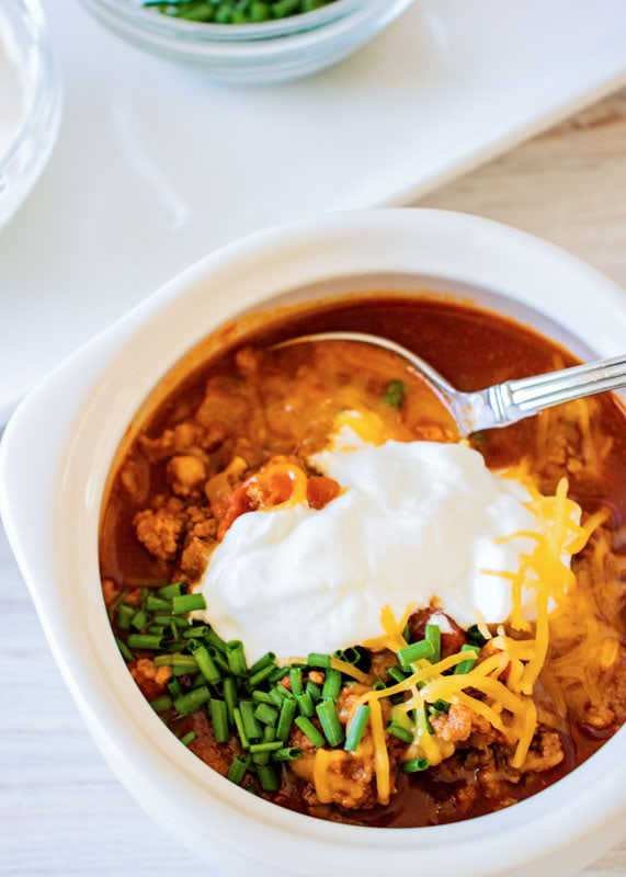 turkey chili topped with sour cream and chives in a bowl