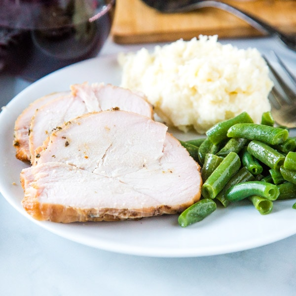 close up sliced turkey breast on plate with potatoes and beans