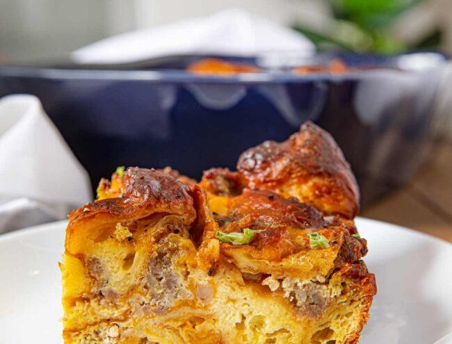 Sausage, Egg and Cheese Breakfast Casserole with Croissants on a white plate