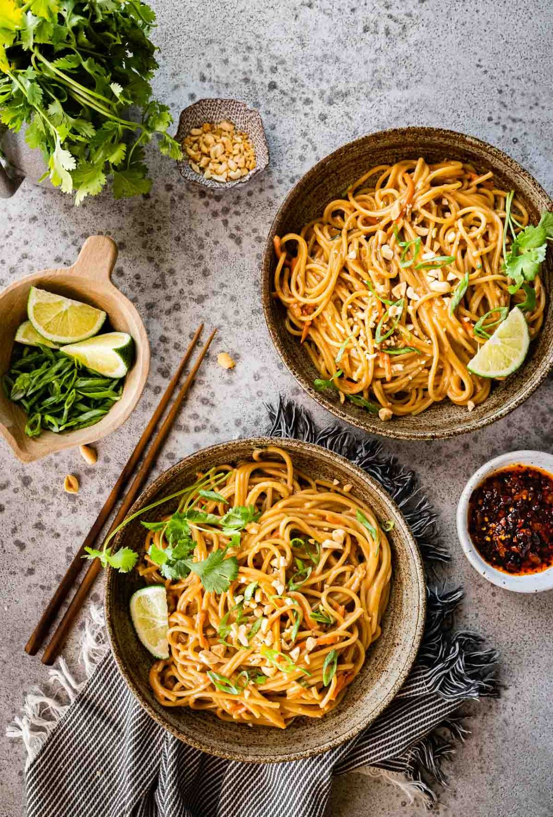 Spicy Peanut Noodles in serving bowls with chop sticks and cilantro lime garnish