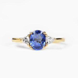 oval Ceylon blue sapphire engagement ring with trillion cut diamonds